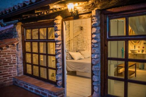 Foto desde la Terraza de la Habitación nº 4 detalle de la cama y pared de adobe, madera y piedra blanca