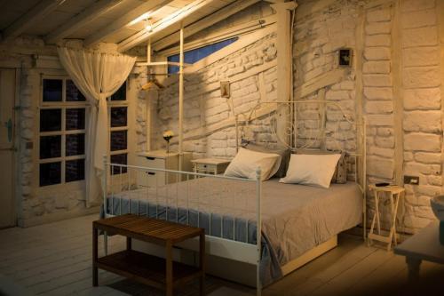 Habitación nº 4 detalle de la cama y pared de adobe, madera y piedra blanca foto de noche
