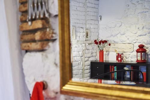 ¿Qué ver y hacer en Vera (Cáceres) y Alrededores ?Jarandilla de la Vera ofrece al viajero un entorno natural, ruta con orquídeas y mariposas. Foto artística de la habitación Juglar o nº1 del espejo y reflejado una botella de champagna, cubitera y claveles rojos